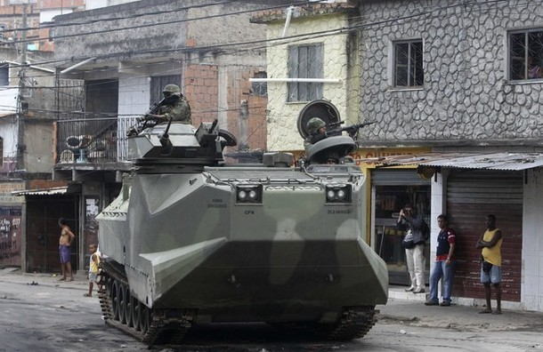 Brazilian army soldiers patrol with an armoured vehicle during an operation at Vila Cruzeiro slum in Rio de Janeiro