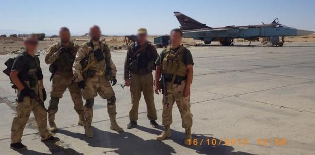 Personal de Slavonic Corps en Siria con un avión de ataque Su-24 a sus espaldas.